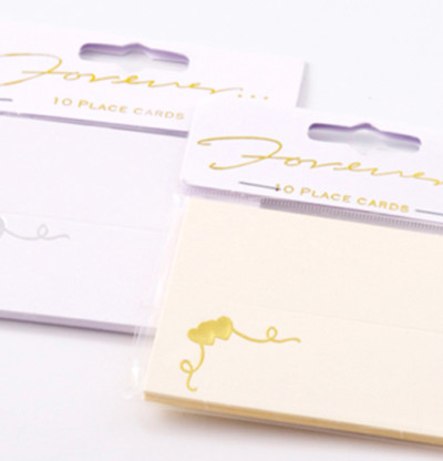 Gold foil embossed printed hearts on a cream place card.